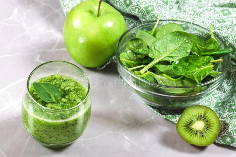 Grüner gesunder Smoothie und eine Schüssel von frischen Spinatsblättern, -kiwi und -apfel stockbild