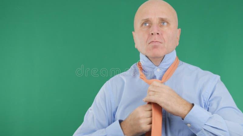 Grüner Hintergrund mit Geschäftsmann Making ein Bindungs-Knoten stockfotografie