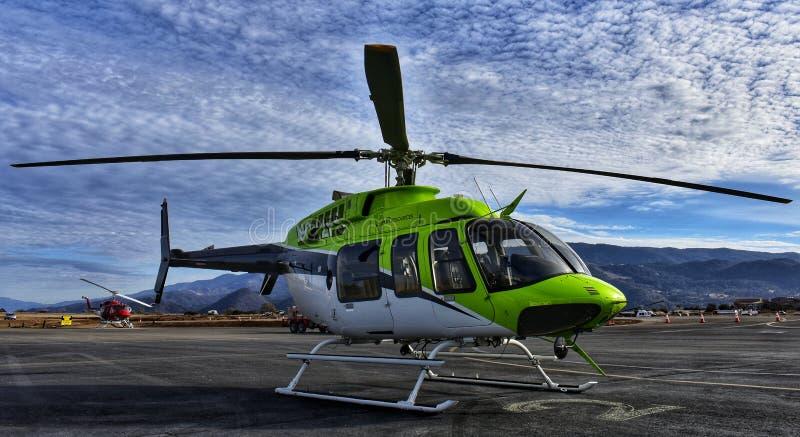Grüner Hubschrauber auf Landebahn stockfotos