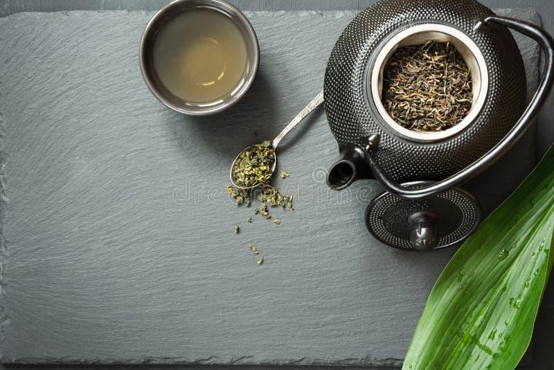 Grüner japanischer Tee auf schwarzem Schiefer Schwarze Teekanne mit trockenem grünem Tee Teevorbereitung Draufsicht mit Kopienrau lizenzfreies stockbild