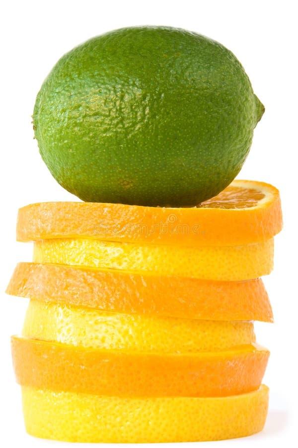Grüner Kalk auf Plättchen der Orangen und der Zitronen. lizenzfreie stockfotos