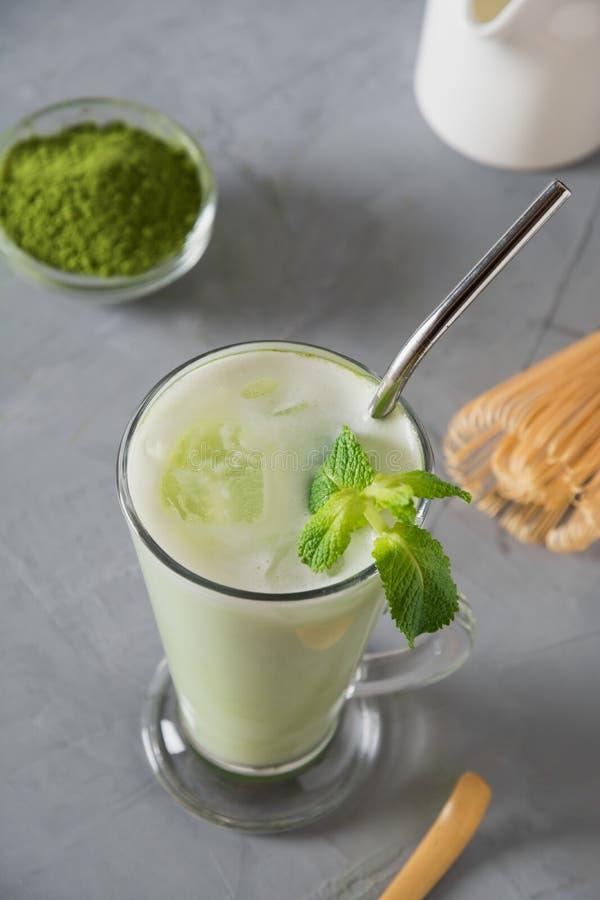 Grüner kalter matcha Tee im Latteglas mit Eiswürfel und -milch auf grauer Tabelle stockfoto