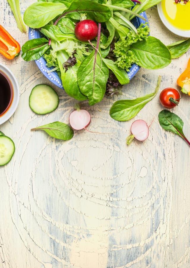 Grüner Landsalatteller mit Rettich, Gurke und Tomaten auf hellem rustikalem Hintergrund, Draufsicht stockfotografie