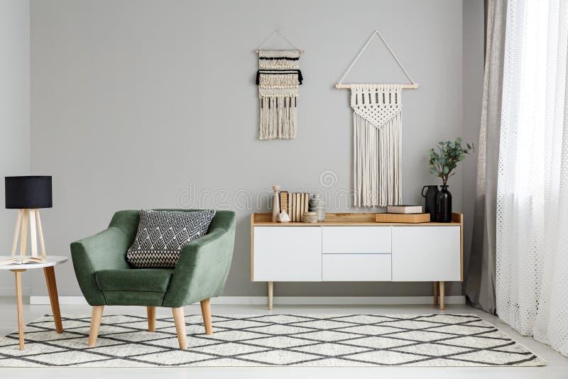 Grüner Lehnsessel auf kopiertem Teppich nahe Tabelle mit Lampe in der halben Note stockbild
