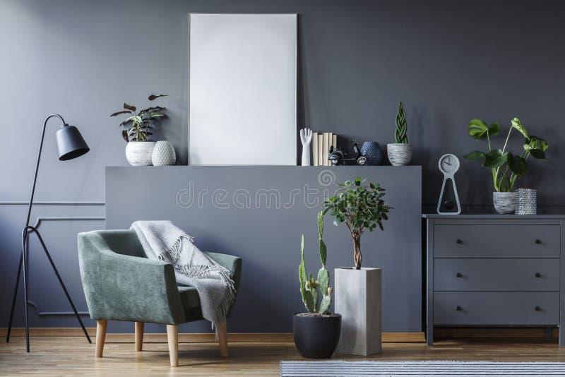 Grüner Lehnsessel zwischen schwarzer Lampe und Anlagen im grauen flachen interi lizenzfreie stockfotos