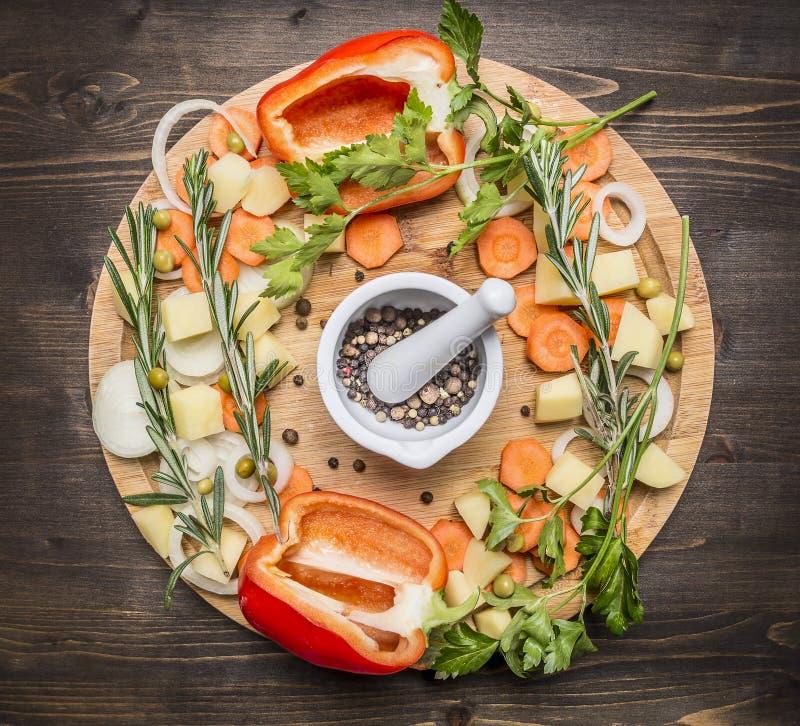Grüner Pfeffer, verschiedener ungemahlener Pfeffer, gehackte Karotten, Kartoffeln und Kräuter auf einer Draufsicht des hölzernen  stockfoto