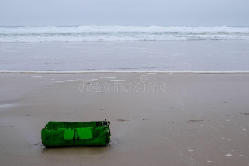 Grüner Plastikbehälter gewaschen oben auf dem Strand auf der Austernfischer-Spur, nahe Mossel-Bucht, Garten-Weg, Südafrika stockbild