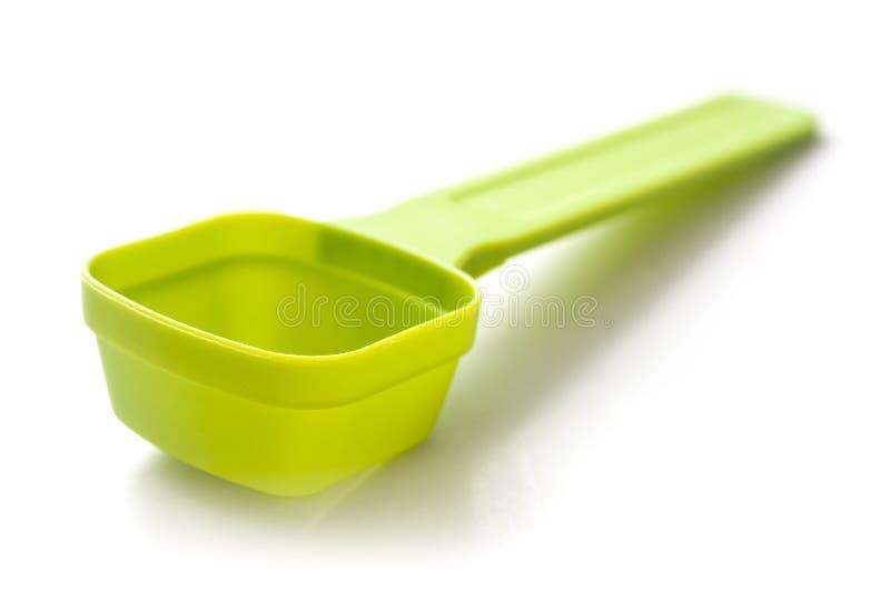 Grüner Plastikdosislöffel auf weißem Hintergrund stockbild