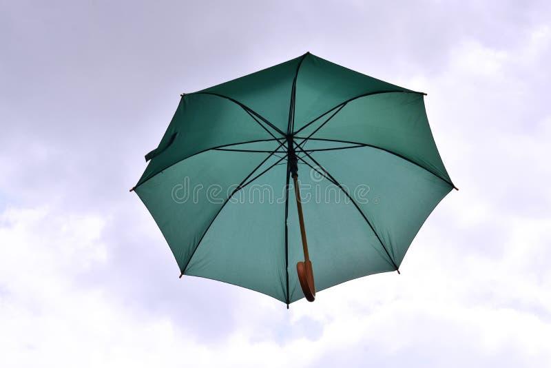 Grüner Regenschirm, der in den Himmel schwimmt lizenzfreie stockfotografie