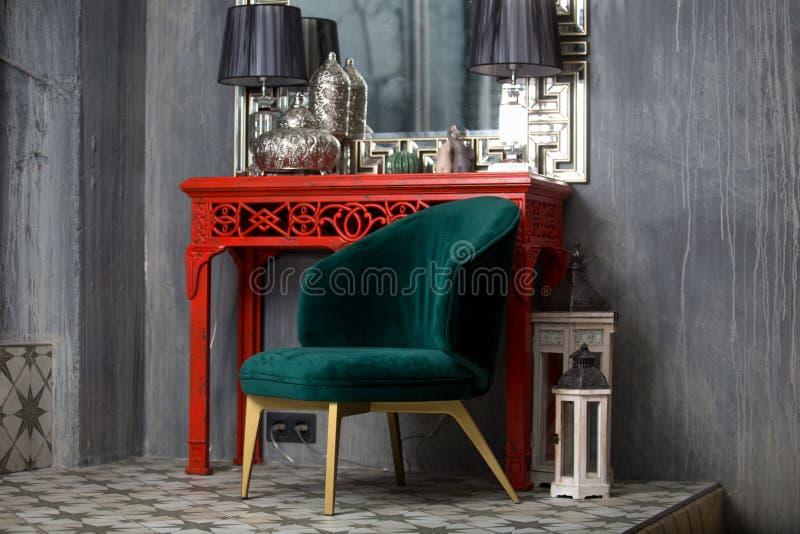 Grüner Retro- Stuhl nahe der roten Frisierkommode stockfoto