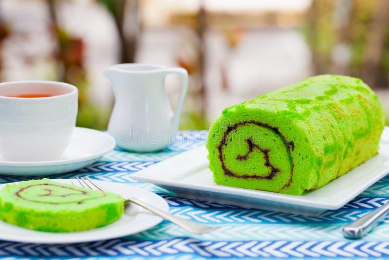 Grüner Rollenkuchen mit einer Tasse Tee Hintergrund des Sommers im Freien Kopieren Sie Platz lizenzfreie stockbilder
