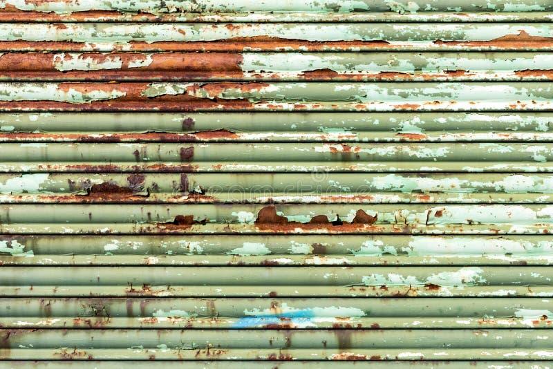 Grüner rostiger Rollenfensterladen stockfoto