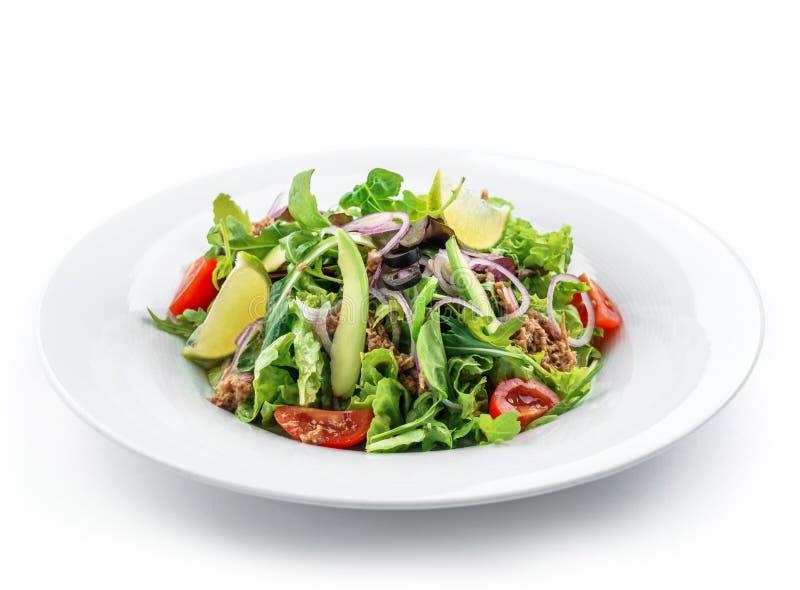 Grüner Salat mit Arugula, Salat, Tomaten, Avocado, Kalk, Thunfisch und Oliven auf dem Teller auf einem weißen Hintergrund. gesun lizenzfreies stockfoto