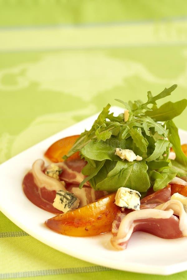 Grüner Salat mit Pfirsichen, Blauschimmelkäse und Schinken lizenzfreie stockfotos