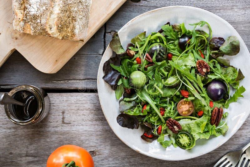 Grüner Salat mit grüner Tomaten-, Pekannuss- und Goji-Beere stockfotografie
