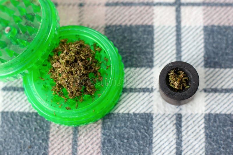 Grüner Schleifer für reibendes Marihuana, frischer geschnittener Hanf lizenzfreie stockfotografie