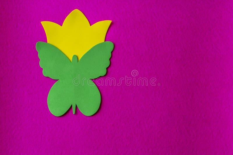 Grüner Schmetterling und gelbe Blume gemacht vom weichen Material auf pinkfarbenem Hintergrund lizenzfreie stockbilder