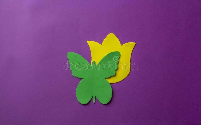 Grüner Schmetterling und gelbe Blume gemacht vom weichen Material auf violettem Hintergrund lizenzfreie stockfotos