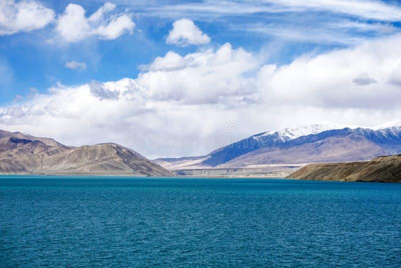 Grüner See, Schneeberg, weiße Wolken, blauer Himmel in Pamirrs lizenzfreies stockfoto