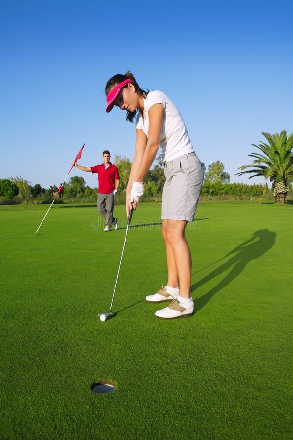 Grüner setzender Loch-Golfball des Golffrauenspielers lizenzfreie stockfotos