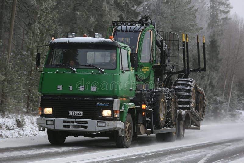 Grüner SISU-LKW schleppt John Deere Forwarder in Winter stockbild