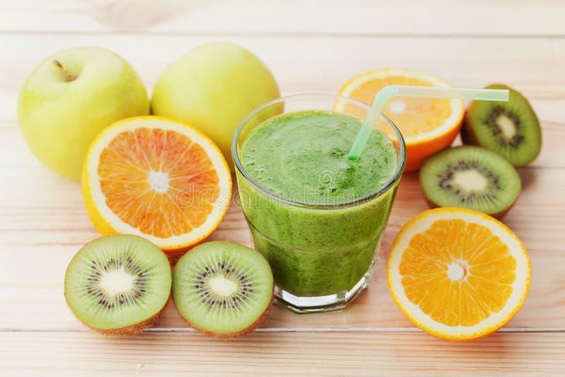 Grüner Smoothie oder Saft im Glas auf Holztisch, Detox und Diätlebensmittel stockfotografie