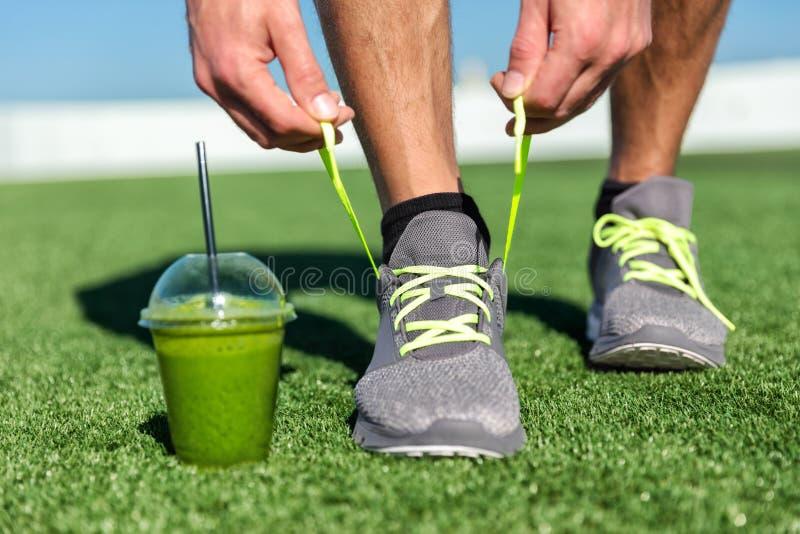 Grüner Smoothieeignungsmann, der Laufschuhe bindet stockbilder