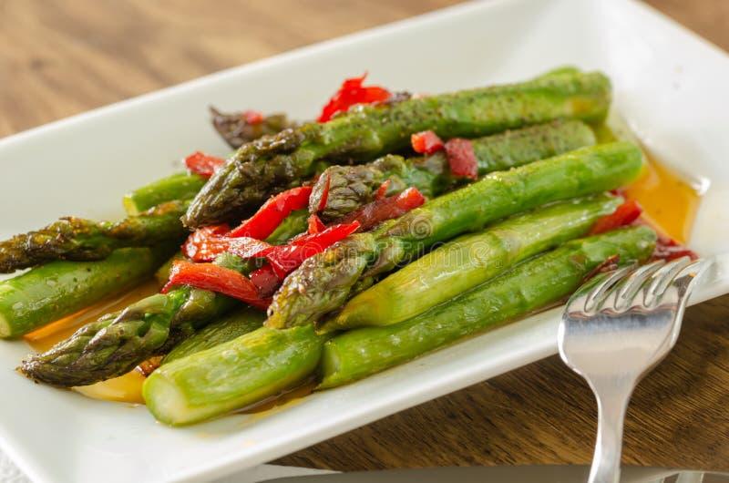 Grüner Spargel sautéed mit dem roten Pfeffer, gedient als Salat lizenzfreies stockfoto