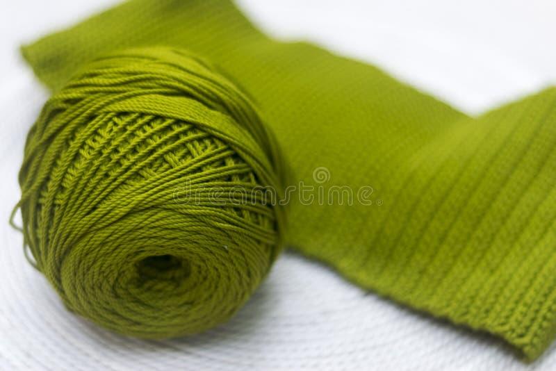 Grüner Strang der Wolle mit einem gestrickten Teil lizenzfreie stockbilder