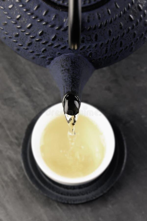 Grüner Tee, der aus einer japanischen Teekanne heraus ausgelaufen wird lizenzfreie stockfotografie