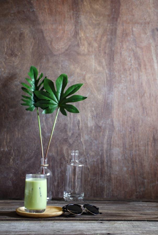 Grüner Tee des Eises auf hölzernem Schreibtisch mit einer Buchanmerkung und -Sonnenbrille stockfoto