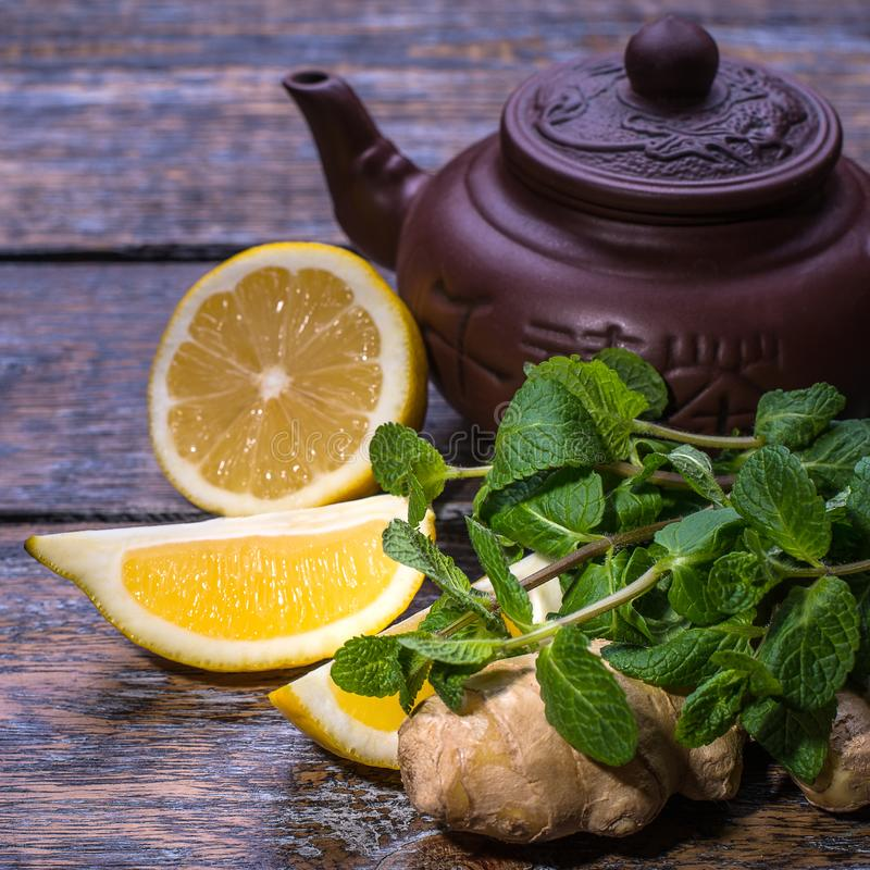 Grüner Tee in einem braunen Topf, Minze, Zitrone, Ingwer auf einem dunklen alten Hintergrund stockbild