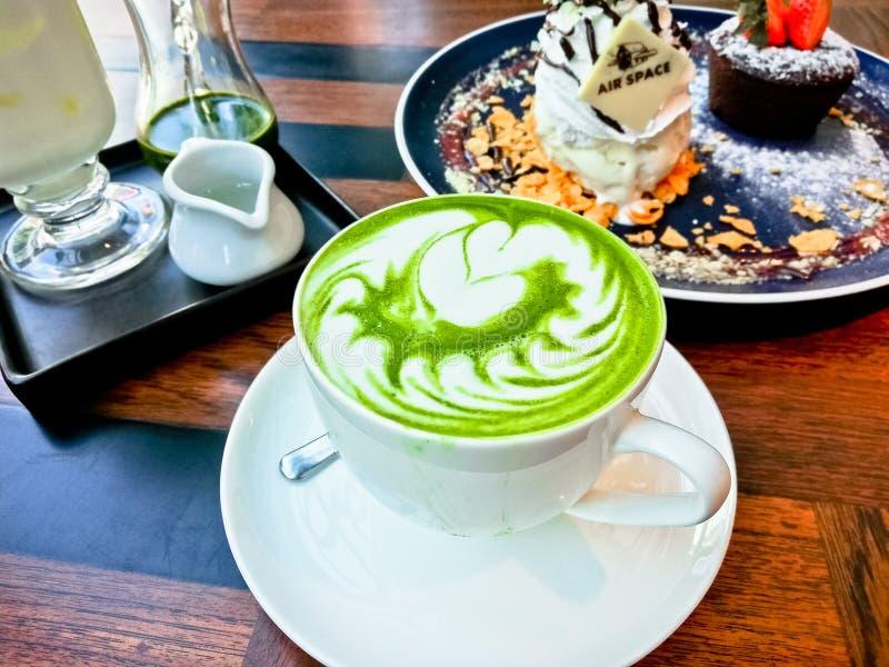 Grüner Tee Latte mit Nachtischen auf Holztisch, Hintergrund des grünen Tees stockfotografie