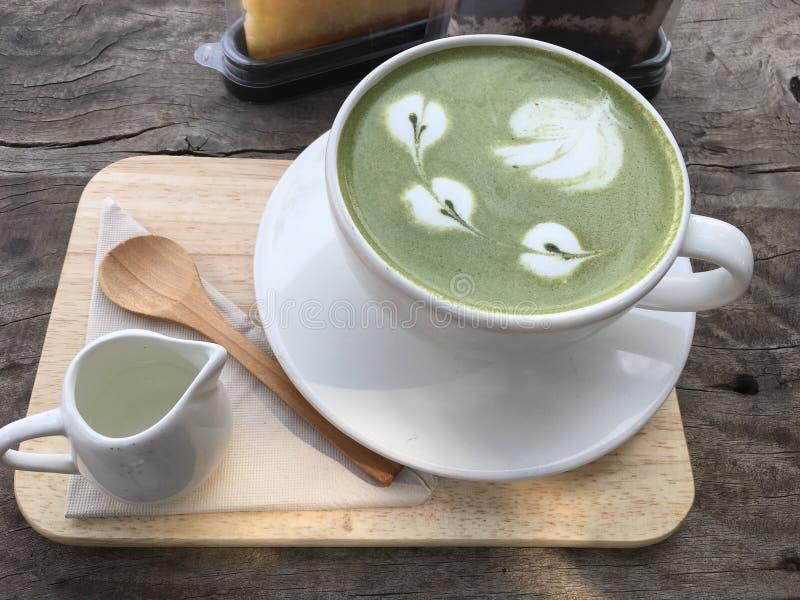 Grüner Tee Matcha-Latte-Kaffee in einer weißen Schale auf hölzernem Behälter stockfotografie