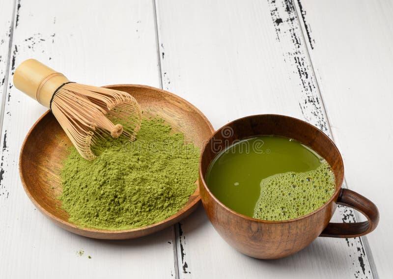 Grüner Tee matcha Pulver in einer hölzernen Schüssel mit wischen und ein matcha Schale des grünen Tees stockfotografie