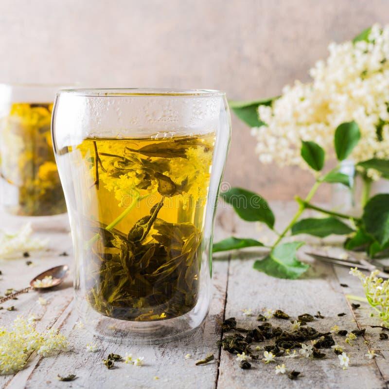 Grüner Tee mit älterer Blume stockbild