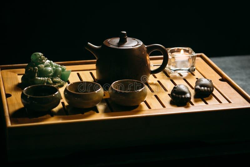 Grüner Tee mit Cup und Teekanne Der Mann gießt heißen chinesischen Tee in die Teeschale stockbild