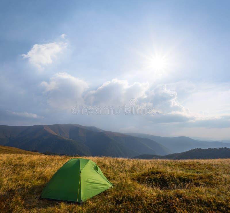 Grüner touristischer Zeltaufenthalt unter einem Bergplateau stockfotos
