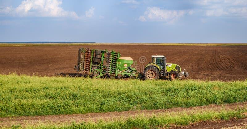 Grüner Traktor der Landwirtschaft, der Samen sät und Feld am späten Nachmittag kultiviert stockfotos