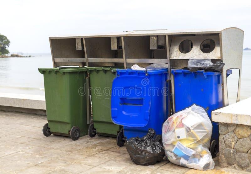 Grüner und blauer Behälter für unterschiedliche Sammlung Recycle Materialien auf Fußweg nahe Strand lizenzfreies stockfoto