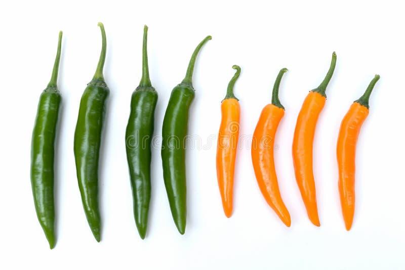 Grüner und orange Paprikapfeffer der Draufsicht auf dem weißen Hintergrund lokalisiert lizenzfreie stockfotos