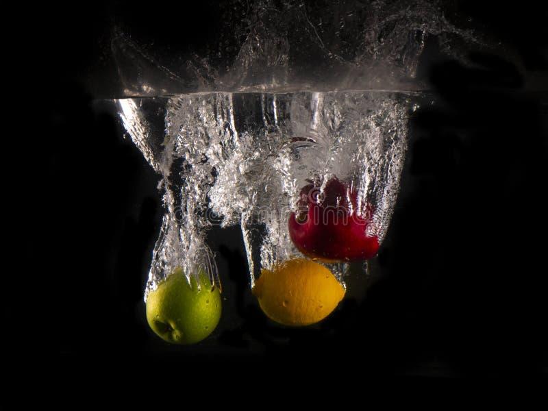 Grüner und roter Apfel, gelbe Zitrone, die in Spritzwasser auf schwarzem Hintergrund fällt stockfoto