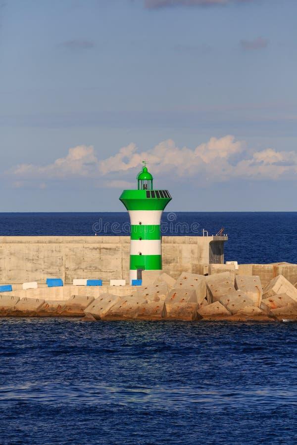 Grüner und weißer Leuchtturm auf Uferdamm stockfotos
