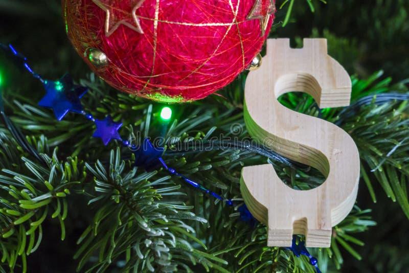 Grüner Weihnachtsbaum mit roten Weinleseballdekorationen und hölzernem Dollarzeichen - Feiertagshintergrund lizenzfreies stockfoto