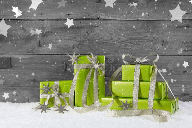 Grüner Weihnachtshintergrund auf grauem hölzernem Hintergrund mit Schnee stockfoto