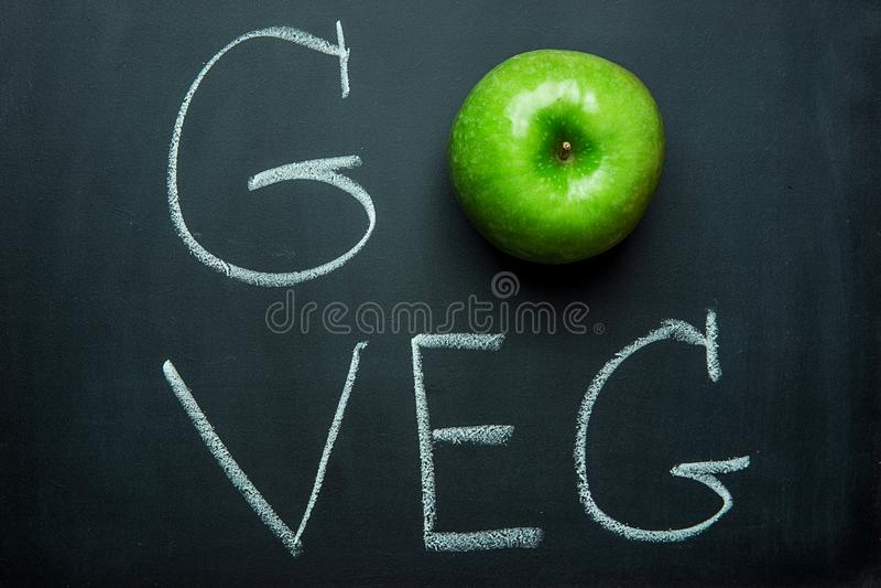 Grünes Apple auf schwarzer Tafel übergeben Beschriftung gehen Veg Vegetarisches Konzept-gesunde Diät Superfood des strengen Veget lizenzfreie stockfotografie
