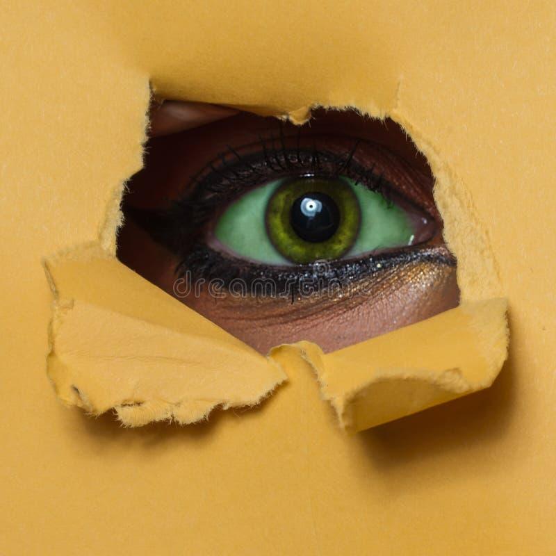 Grünes Auge durch ein Loch lizenzfreies stockfoto