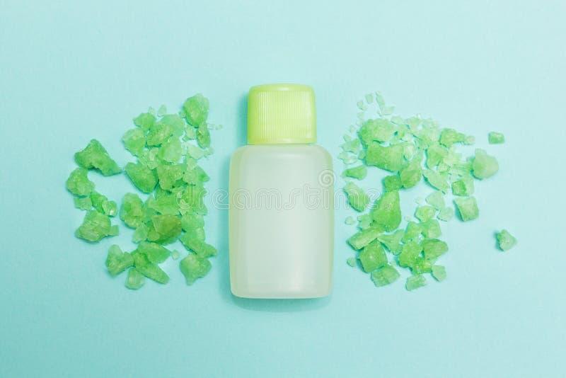 Grünes Badesalz und aromatisches Öl auf einem blauen Hintergrund stockbild