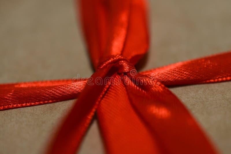 Grünes Blatt mit einem großen Wassertropfen Nah - oben vom roten Bogen und von den Bändern vom Geschenkhandwerksverpacken stockbild