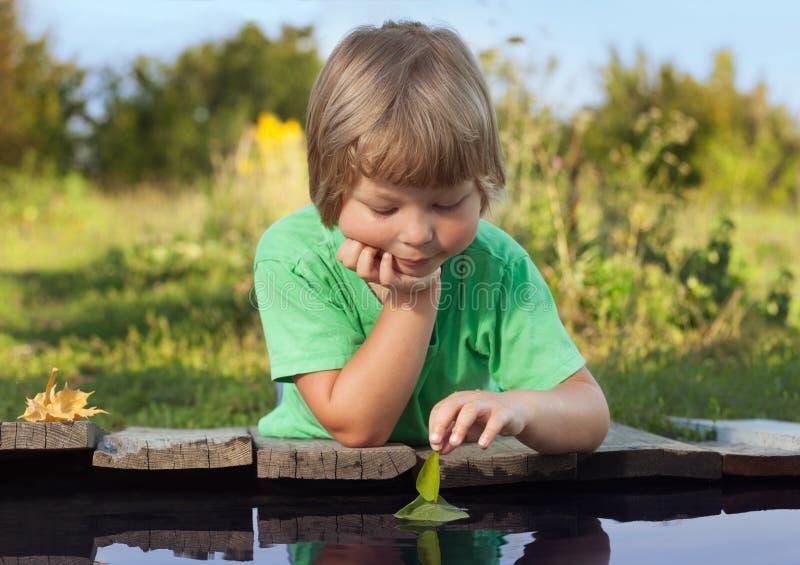 Grünes Blattschiff in der Kinderhand im Wasser, Junge im Parkspiel mit stockfoto